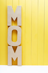 MOM text letters on yellow wooden background