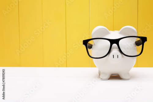 Piggy bank with glasses over yellow wooden wall - 78019243