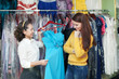 girl chooses evening dress at clothing boutique