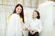 Girl chooses bridal veil at shop of wedding fashion