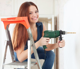 Happy girl drills hole in the wall