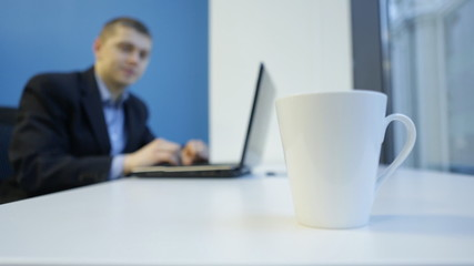 Man typing on a laptop and a cup