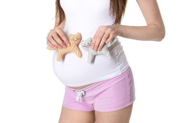 Young pregnant woman holding toys in front of her belly.
