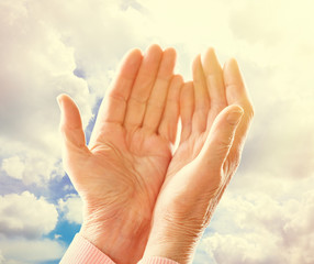 Hands of old woman on clouds background