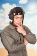 young handsome pilot wearing uniform and helmet over beach