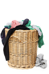 Dirty clothes loundry in wicker basket, frontal, isolated on whi