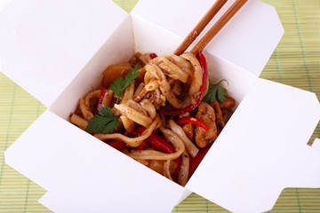 Fried noodles in takeaway box on mat background