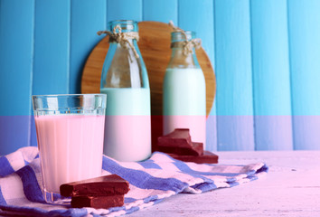 Glass and bottles of milk with chocolate chunks