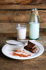 Glass and bottle of milk with chocolate chunks