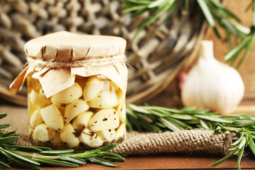 Canned garlic in glass jar and wicker mat and rosemary