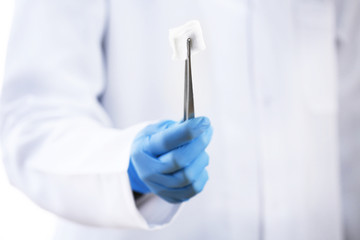 Doctor holding metal forceps with cheesecloth