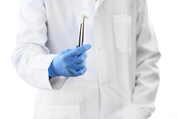 Doctor holding metal forceps with cheesecloth isolated