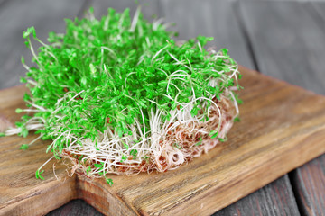 Fresh cress salad on cutting board and wooden planks background