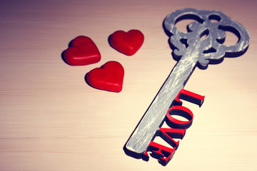 Retro key with hearts and word Love on wooden table background