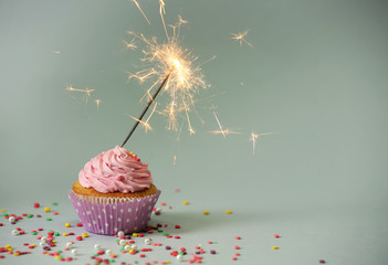 Cupcake with sparkler on grey background