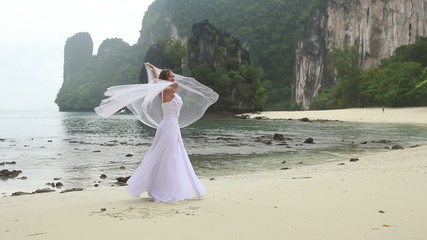 young blonde bride turns around barefoot with veil sandy beache
