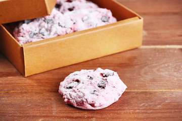 Pink cookies in paper box on table close-up