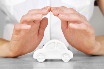 Hands and toy car. Protection of car concept