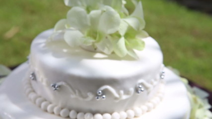 closeup fresh white orchid and beads decorated wedding cake with