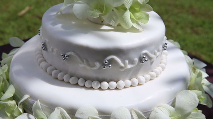fresh white orchid and beads decorated wedding cake with green g