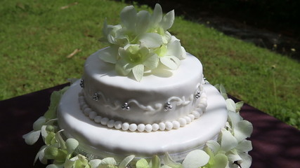 rotate fresh white orchid and beads decorated wedding cake with