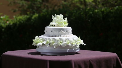 zoom on fresh white orchid and beads decorated wedding cake with