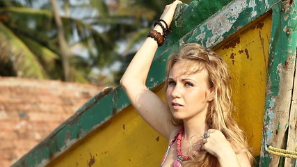 posing for camera and leans back on wooden boat on sandy beach