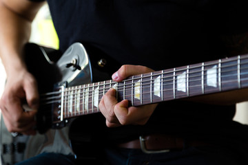 Guitarist play on black electric guitar