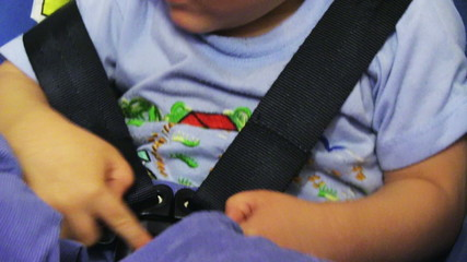 Little baby fastened with security belt in safety car seat