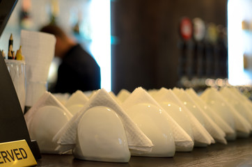 White crockery and napkins on a bar counter