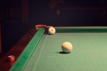 White Pool Ball on Billiard Table Near the Hole