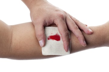 human hand holding bandage on wrist with blood on it