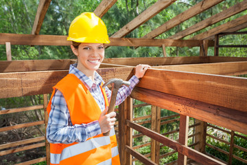 Confident Female Worker Holding Hammer In Timber Frame