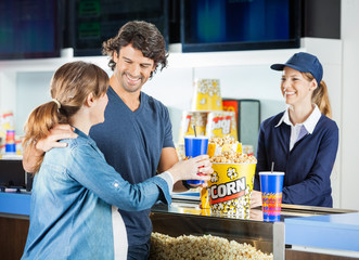 Expectant Couple Buying Snacks At Concession Stand
