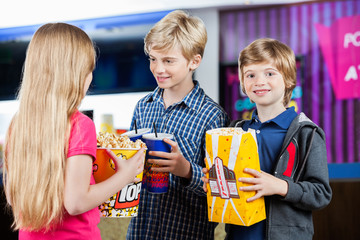 Boy Holding Popcorn While Siblings Talking At Cinema