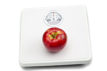 scale with apple on white background