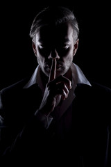 Men's silhouette in the dark shows silence gesture