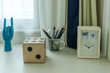 decorative table with pencils and clock in room