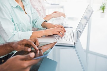 Coworkers using laptop and tablet at desk