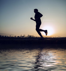 Runner sunset silhouette with mirror in water