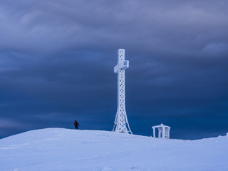 Summit cross and hiker, mount Catria, Winter, Apennines,Italy