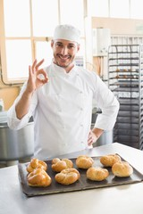 Happy baker showing tray of rolls