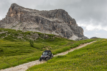 Dune buggy on a trail in the meadows, Dolomites, Italy