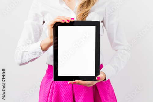 Leinwanddruck Bild Woman holding ipad with empty white screen vertically