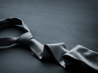 Grey tie on dark background