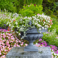 flower bed and stone vase with flowers