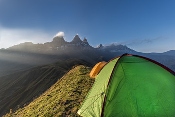 Tents on a mountain edge in front of the Aiguille d'Arves at sun