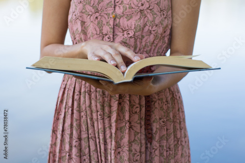 Poster Young woman reading bible in natural park
