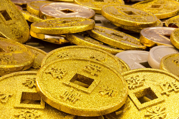 Chinese coins of gold color shot close-up cues