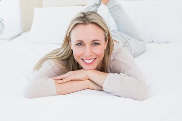 Smiling blonde lying on the bed looking at camera